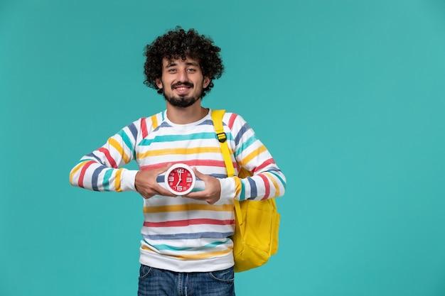 Vista frontale di uno studente maschio in camicia a righe che indossa uno zaino giallo che tiene gli orologi sulla parete blu