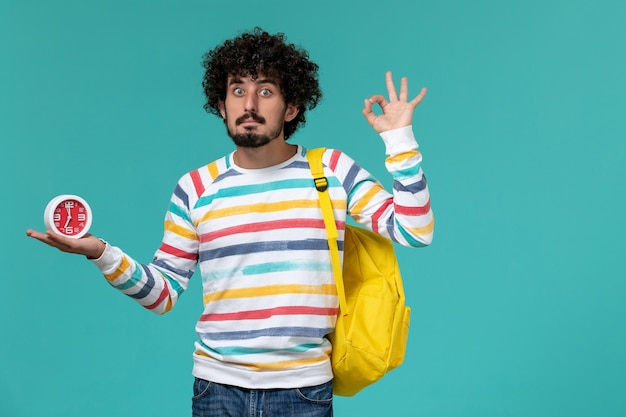 Front view of male student in striped shirt wearing yellow backpack holding clocks on blue wall