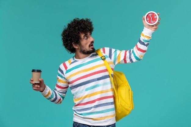 Vista frontale dello studente maschio in camicia a righe che porta zaino giallo che tiene caffè e orologi sulla parete blu