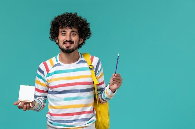 Vista frontale di uno studente maschio in camicia a righe che indossa uno zaino giallo che tiene il cavalletto e la nappa sulla parete blu