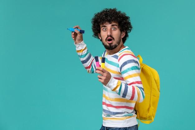 Vista frontale dell'allievo maschio in camicia a strisce che porta zaino giallo che tiene i pennarelli sulla parete blu