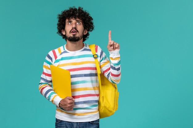Vista frontale di uno studente maschio in camicia a righe che indossa lo zaino giallo che tiene i file sulla parete blu