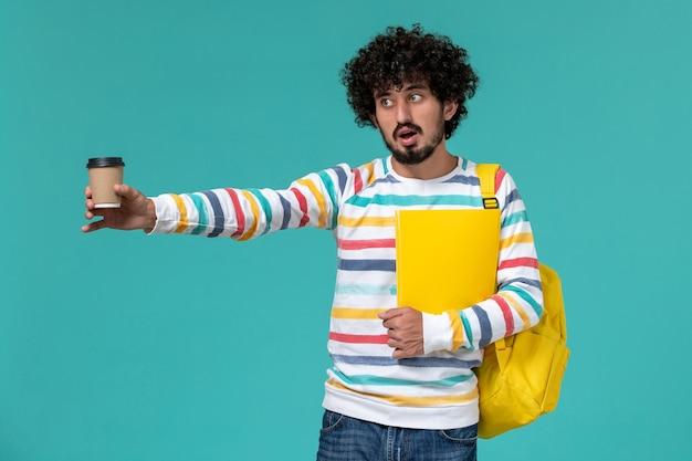 Vista frontale di uno studente maschio in camicia a righe che indossa lo zaino giallo che tiene file e caffè sulla parete blu