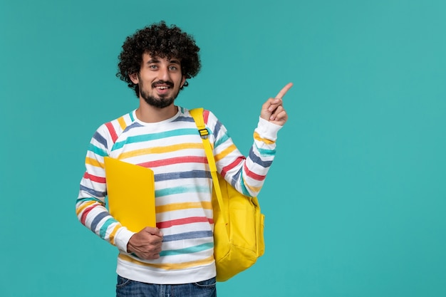 Front view of male student in striped shirt wearing yellow backpack holding files smiling on blue wall