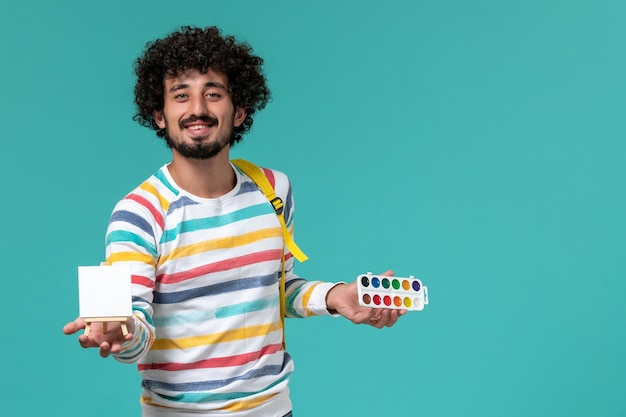 Front view of male student in striped shirt wearing yellow backpack holding paints and easel on the blue wall