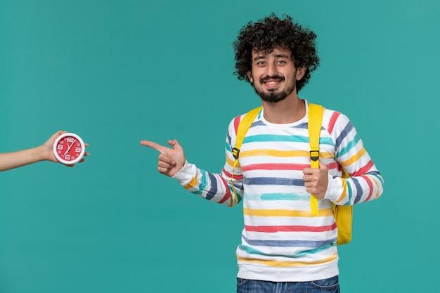 Vista frontale di uno studente maschio in camicia a righe che indossa uno zaino giallo in posa sorridente sulla parete blu chiaro