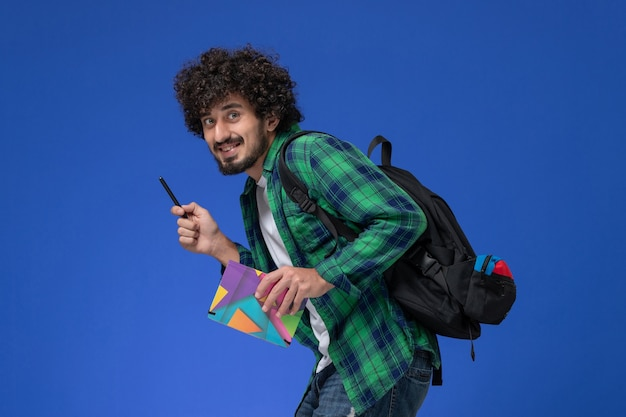 Front view of male student wearing black backpack holding copybook and pen on light-blue wall