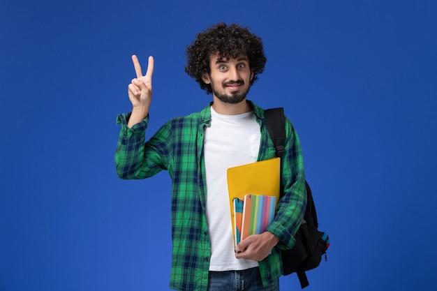 Vista frontale di uno studente maschio che indossa uno zaino nero con quaderni e file sulla parete blu