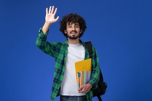Vista frontale di uno studente maschio che indossa uno zaino nero che tiene i quaderni e file agitando la mano sulla parete blu