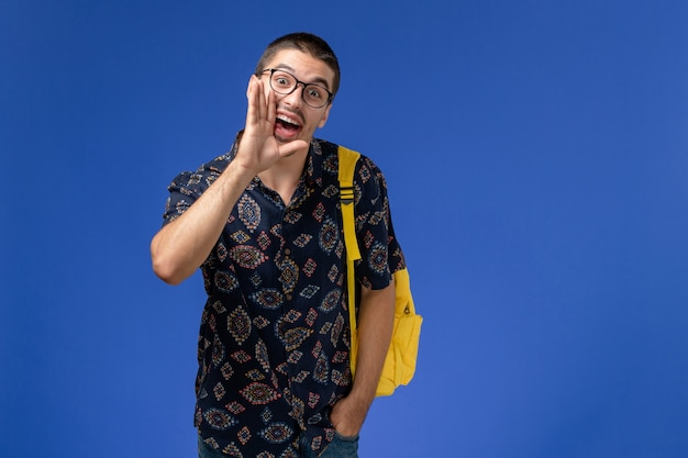 Front view of male student wearing yellow backpack calling out on the blue wall
