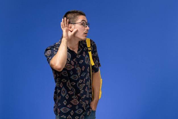 Vista frontale di uno studente maschio che indossa uno zaino giallo cercando di ascoltare sulla parete blu