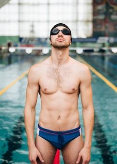 Вид спереди мужской пловец готов к соревнованиям