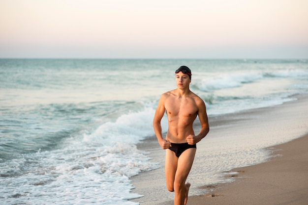 Front view of male swimmer running on beach