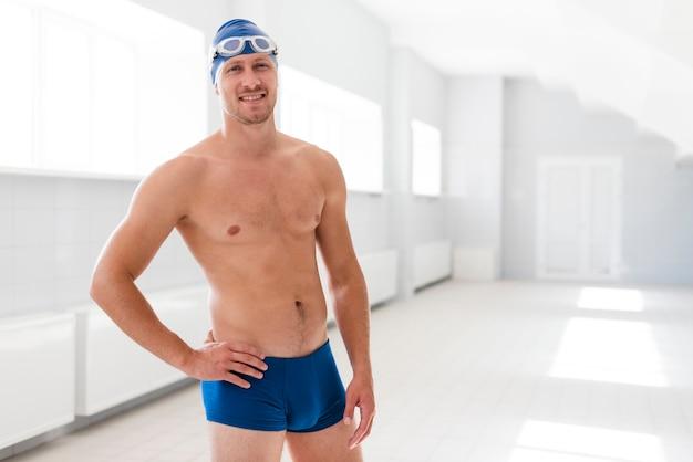 Вид спереди пловец мужского пола, стоящий у бассейна