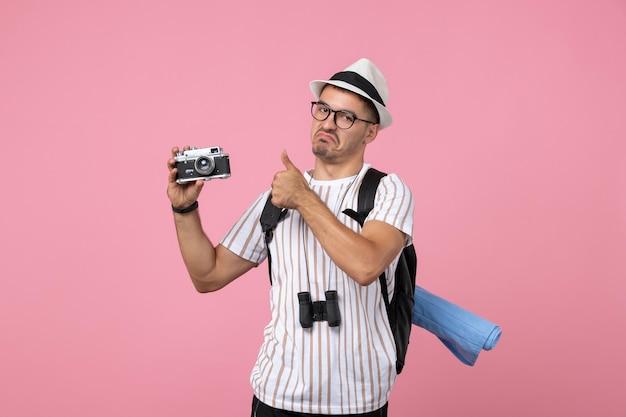 ピンクの机の上のカメラを保持している正面図男性観光客感情観光客の色