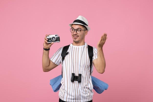 분홍색 벽 감정 관광 색상에 카메라를 들고 전면 보기 남성 관광객