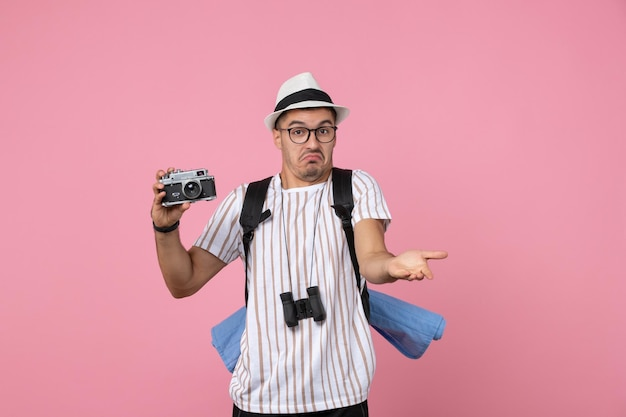 Front view male tourist holding camera for photos on pink wall emotion tourist color