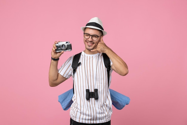 Front view male tourist holding camera on pink wall emotion tourist color
