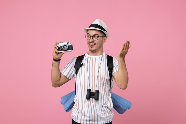 Front view male tourist holding camera on pink wall emotions tourist color