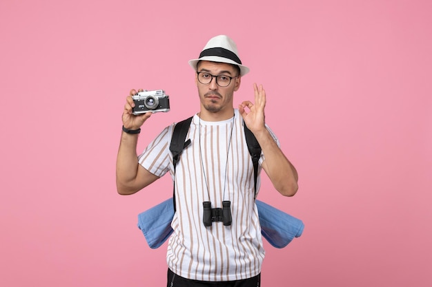 Front view male tourist holding camera on pink wall tourist emotion color