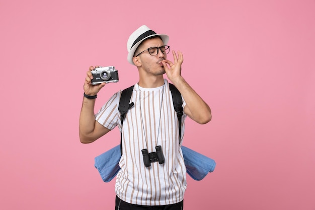 Front view male tourist holding camera on pink wall tourist emotions color