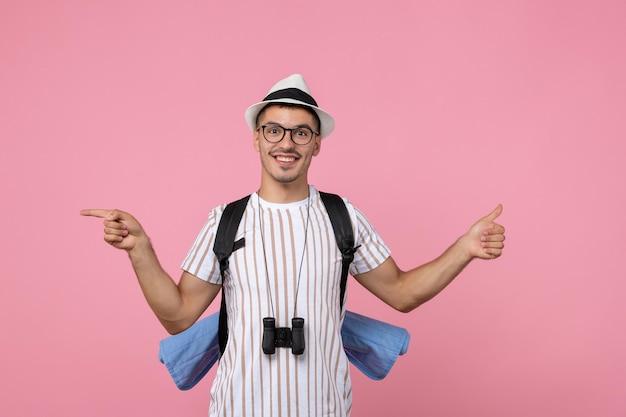 Вид спереди мужской турист позирует с рюкзаком на розовой стене цвет эмоции турист