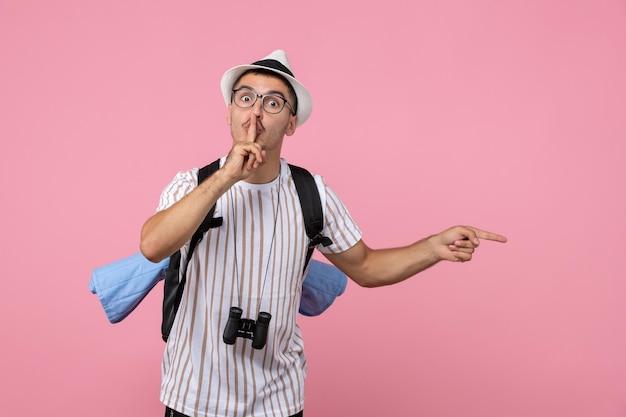 Вид спереди мужской турист позирует с рюкзаком на розовой стене эмоции туристического цвета