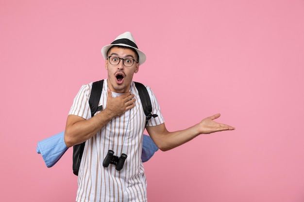 ピンクの壁の感情の観光客の色にバックパックでポーズをとる正面図男性観光客