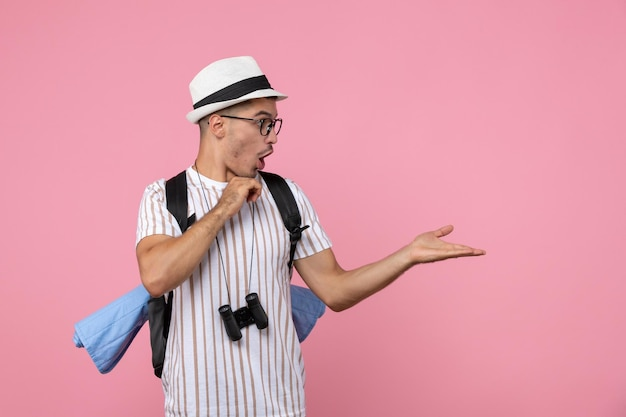 ピンクの机の上のバックパックでポーズをとる正面図男性観光客感情観光客の色