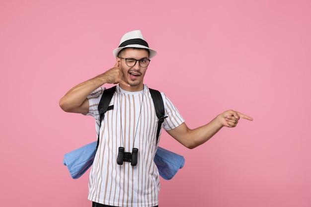 Вид спереди мужской турист позирует с рюкзаком на розовой стене цветные эмоции туриста