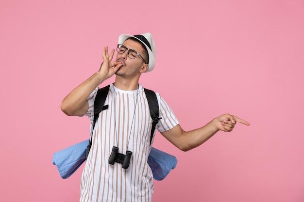 ピンクの壁の感情の観光客の色にバックパックでポーズをとって正面図男性観光客