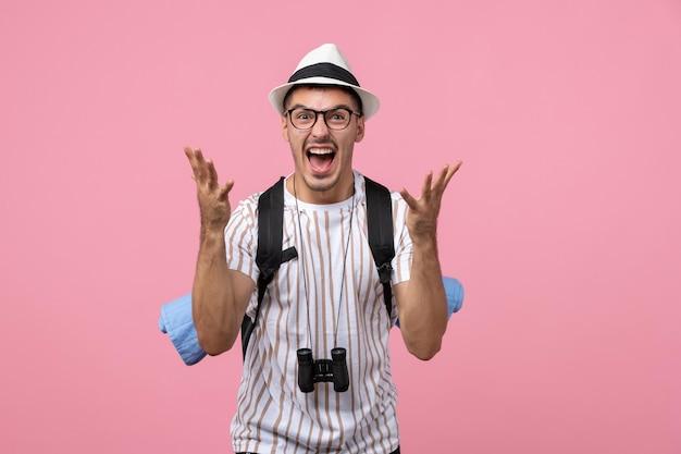 Turista maschio di vista frontale che grida sul turista di emozione di colore rosa della parete