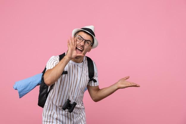 Turista maschio di vista frontale che grida sul colore rosa del turista di emozione della parete