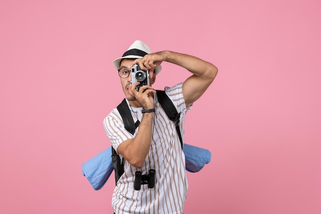 Вид спереди мужской турист, фотографирующий с камерой на розовой стене туристического цвета эмоции
