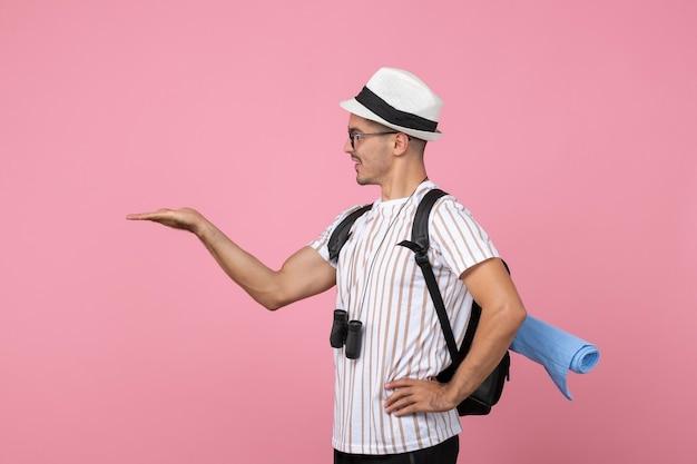 ピンクの壁の色の感情の観光客にバックパックを持って歩く正面図男性観光客