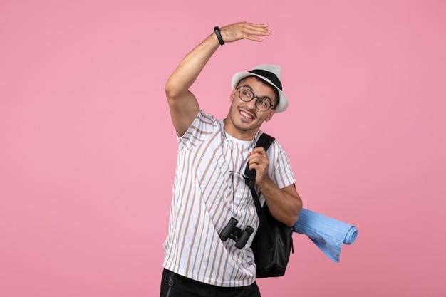 Вид спереди мужской турист с рюкзаком на розовой стене цвет туристической эмоции