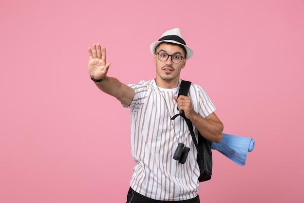 분홍색 벽 색 관광 감정에 배낭을 메고 전면 보기 남성 관광객