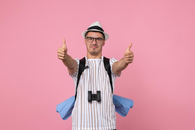 Turista maschio di vista frontale con il suo zaino sul turista di emozione di colore rosa della parete