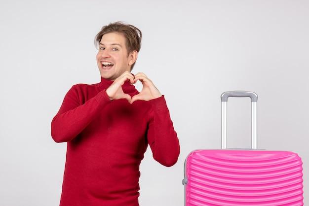 Vista frontale del turista maschio con borsa rosa sul muro bianco