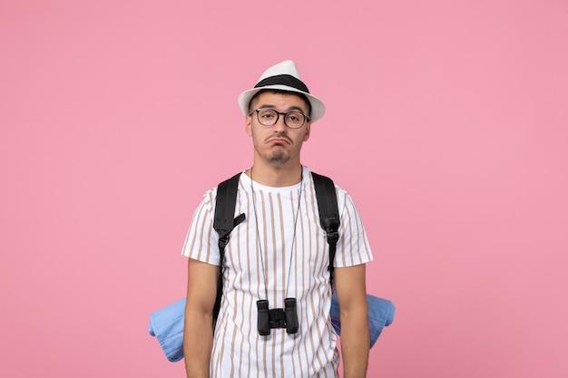 Вид спереди мужской турист с грустным выражением лица на розовой стене цвет эмоции турист