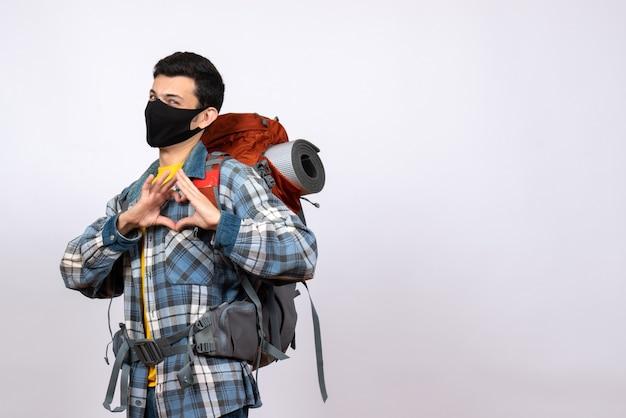 ハートのサインを作るバックパックとマスクと正面図男性旅行者