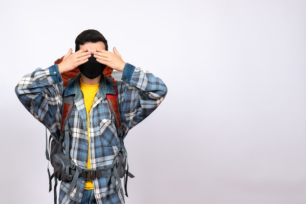 Front view male traveler with backpack and mask covering eyes with hands