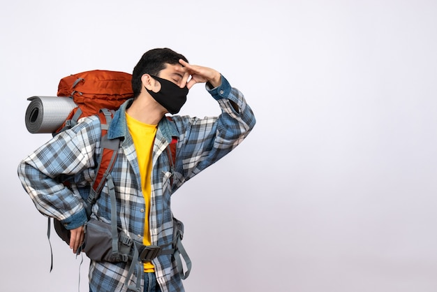 Viaggiatore maschio vista frontale con zaino e maschera tenendo il naso con gli occhi chiusi