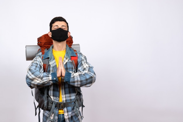 Front view male traveler with backpack and mask joining hands together