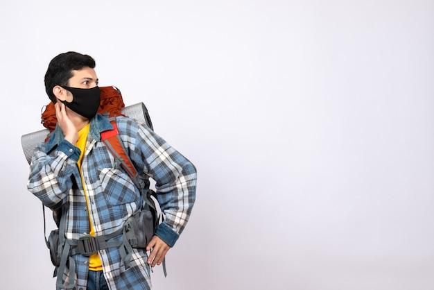 Viaggiatore maschio vista frontale con zaino e maschera guardando a destra