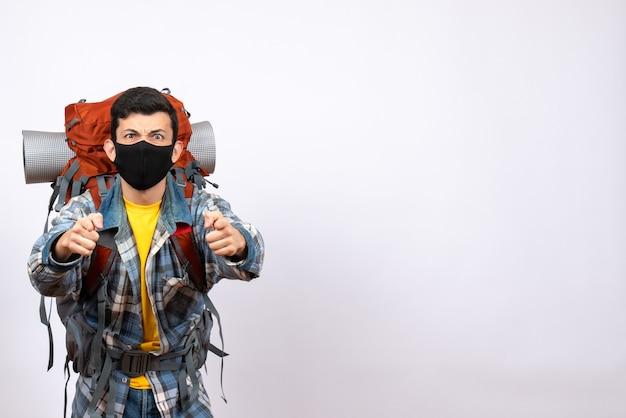 Viaggiatore maschio vista frontale con zaino e maschera che punta alla telecamera