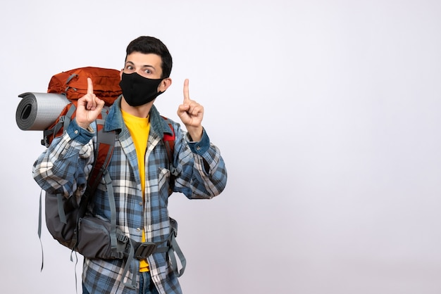 Front view male traveler with backpack and mask pointing fingers up
