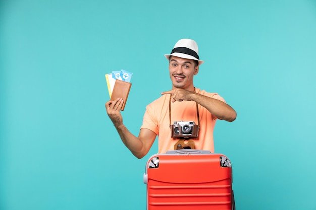 Front view male in vacation holding his tickets and smiling on blue