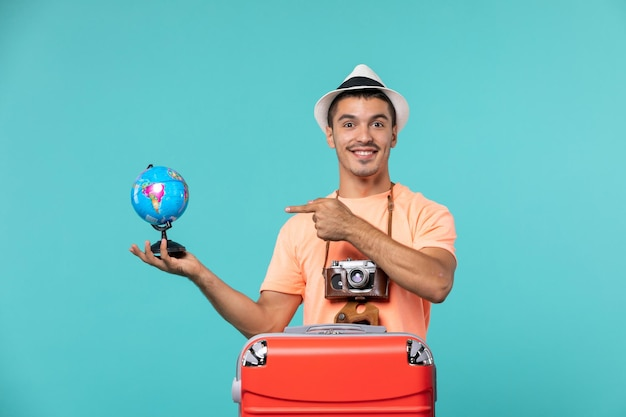 Front view male in vacation holding little globe and smiling on blue