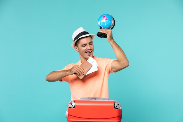 Front view male in vacation holding little globe and tickets on blue